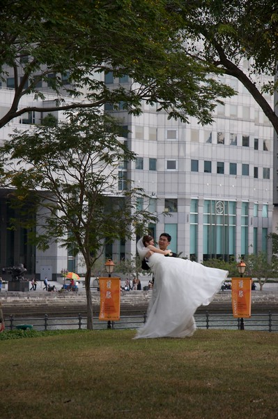 Wedding photo • A newly-married couple have their photo taken on the bank of the Singapore River.
