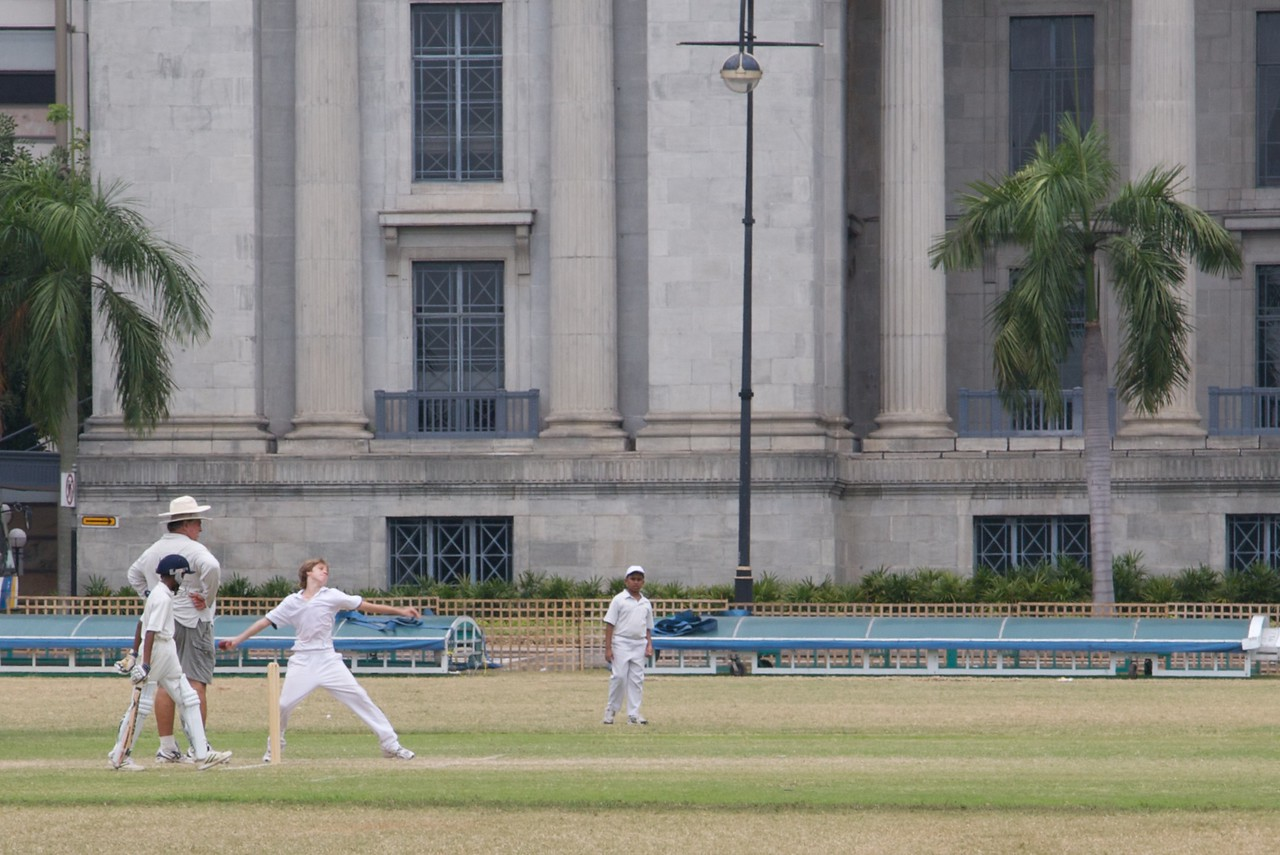 Bowling • A schoolboy bowls during a Sunday afternoon cricket match in the recreation ground on the Padang in Singapore.