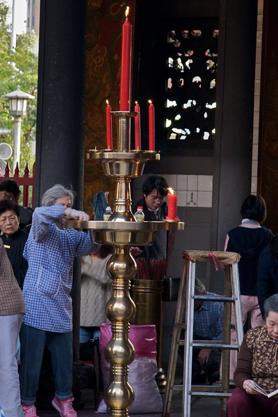Cleaning • A temple warden cleans the wax from a large brass candlestick at Longshan Temple.