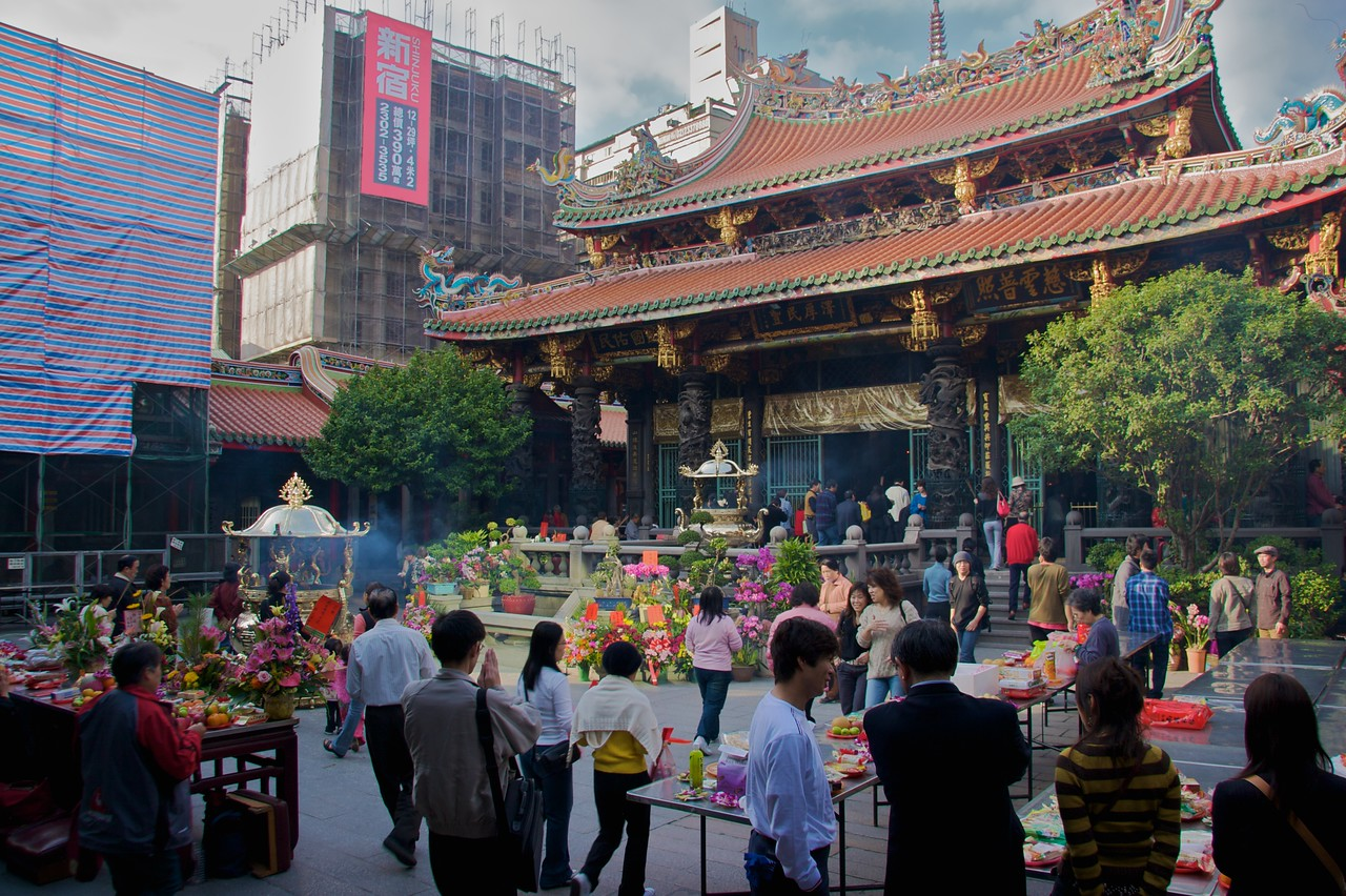 Longshan Temple inner courtyard • Having got through into the first courtyard of the temple, I discovered that it was awash with people. Note the two enormous stand-alone incense burners—the whole area reeked of the sweet smoke, and yet I didn't see anyone reaching to cover their faces, going into coughing fits, etc.!