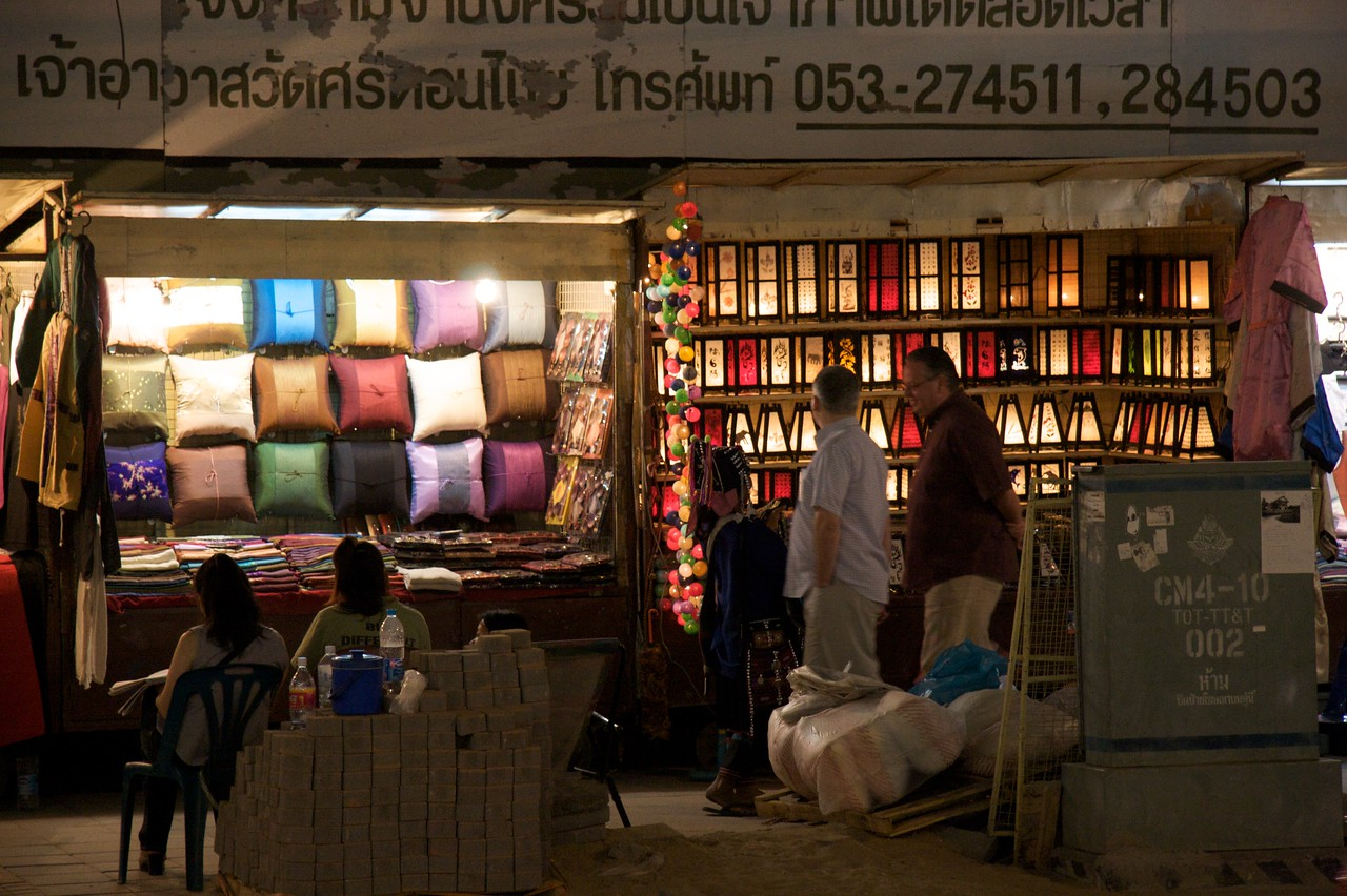 Cushions and Lamps • Some tourists examine lamps on sale at Chiang Mai night market.