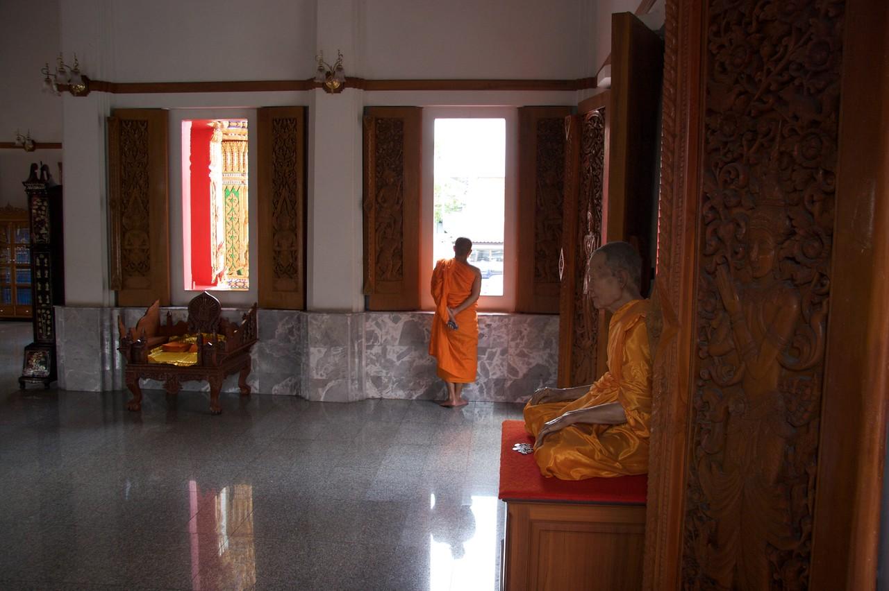 Monks • Two Buddhist monks, one meditating, in Wat Thewarat Kunchon in Bangkok.