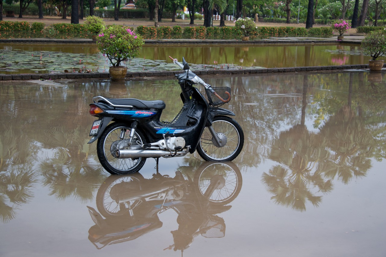 Motorcycle • A motorocycle parked by its owner after the heavy rain at Sukhothai Historical Park.