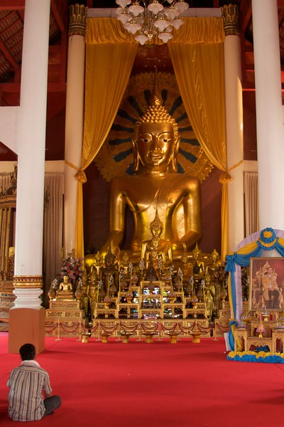 Observer • A man sits cross-legged in front of a statue of Buddha at Wat Phra Singh in Chiang Mai.