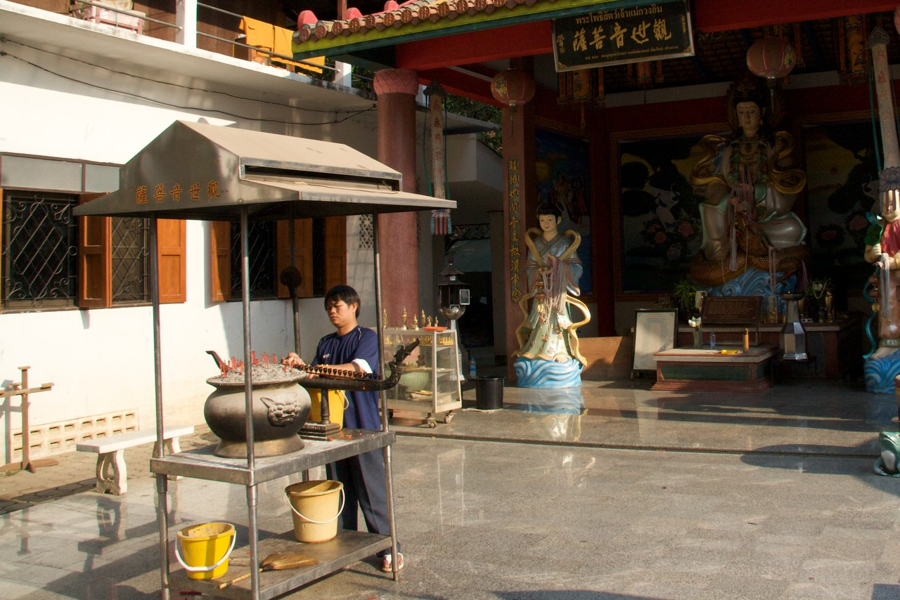 Temple-hand • A man tends to the incense at Wat Chaimongkol in Chiang Mai.