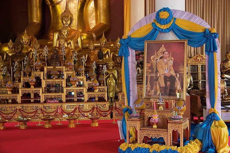 King Rama IX • A portrait of King Rama IX, the King of Thailand, takes pride of place before the statue of Buddha at Wat Phra Singh in Chiang Mai. The King represents the head and protector of Buddhism in Thailand.