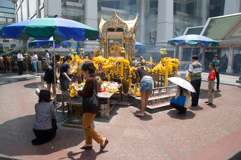 Erawan Shrine • The Erawan Shrine, a shrine very much 'in the city' of Bangkok, being situated at a busy crossroads surrounded with a low fence such that the hubbub of traffic and people going past isn't blocked out.