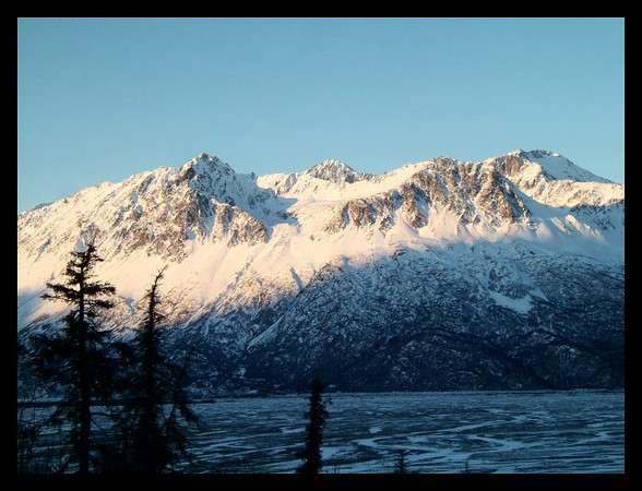 Icy mountains look down on the Knik River Valley during a frigid January morning.