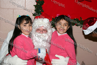 Twins have their picture taken with Santa Claus