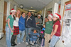 Volunteers Pam, Jenn, Grelen and Mackensie escort families to see Santa and Mrs Claus at the annual St Mary's Christmas party
