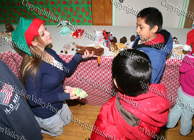 Maria hands out beanie babies to the kids at the annual St Mary's Christmas party
