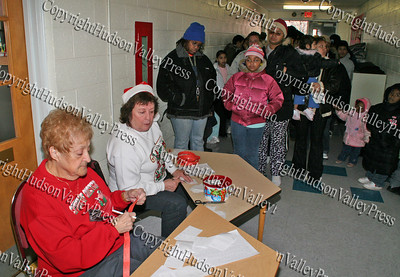 Volunteers Josie and Lilly hand out tickets to see Santa and Mrs Claus during the annual Christmas party at St. Mary's Church in Newburgh