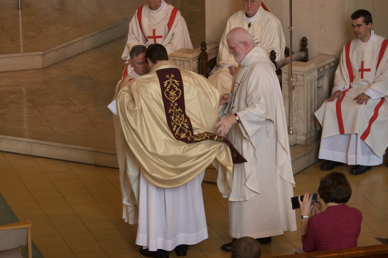 John is clothed in a priest's stole and chasuble.
