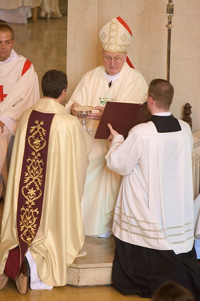 Presentation of the gifts • The Bishop presents the Eucharistic gifts to the new priest.