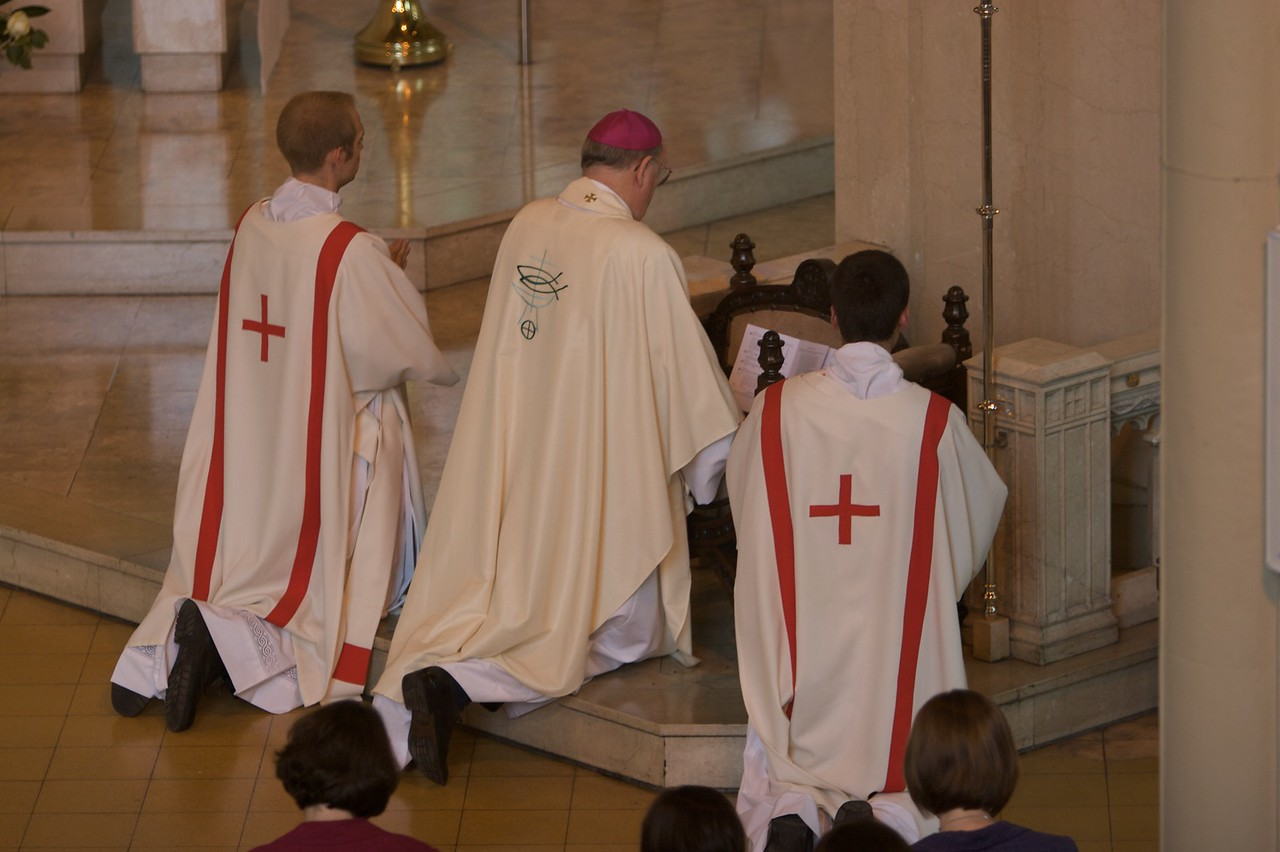 The Litany of the Saints • The Bishop and two deacons kneel during the Litany of the Saints.