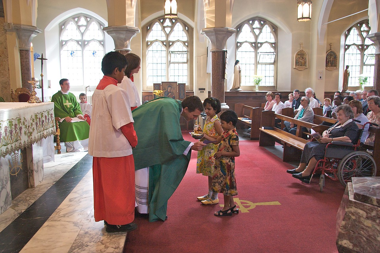 Offertory • At the first Mass which John said in Rusholme the day after his Ordination. At the Offertory, the gifts were brought forward by two children from the parish at Rusholme. You can see one of the little girls giving John a greetings card with the gifts.