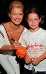 Karolina Muller autographs a mini basketball for a young patron