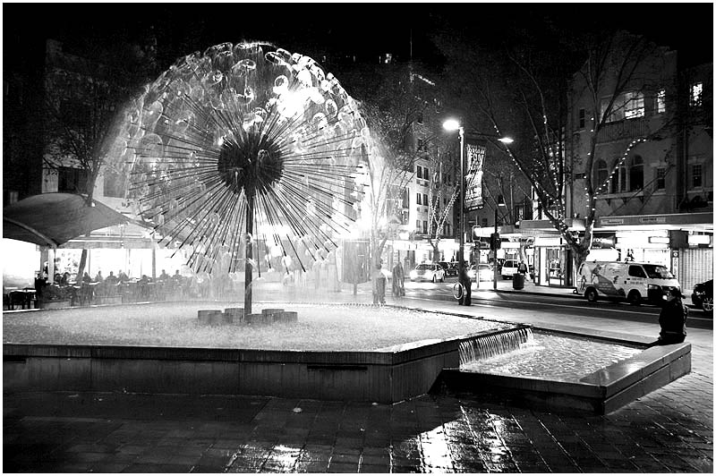 Kings Cross, Friday June 2nd 2006. <br /> <br /> The El Alamein Fountain, designed by Robert Woodward, creates a circle of mist on top of a stem. It was built in 1961 to commemorate the Australian Army's role during the WWII battles at Tobruk in Libya and El Alamein in Egypt. <br /> <br /> EXIF DATA <br /> Canon 1D Mk II. EF 17-35 f/2.8L@30mm 1/30s f/3.2 ISO 1600.