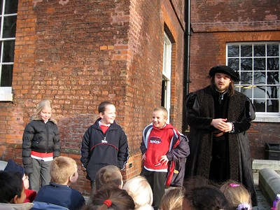 A historical interpreter teaches a group of schoolchildren about the history of the Tower.