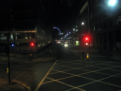 An intersection in London, as seen from the top of a double-decker bus.  The London Eye is visible in the background.