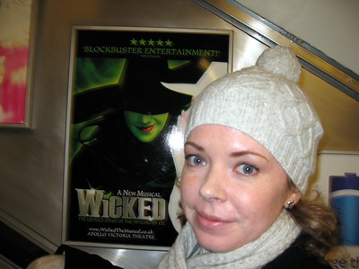 On a tube station escalator, Sarah passes a poster for the London production of Wicked.