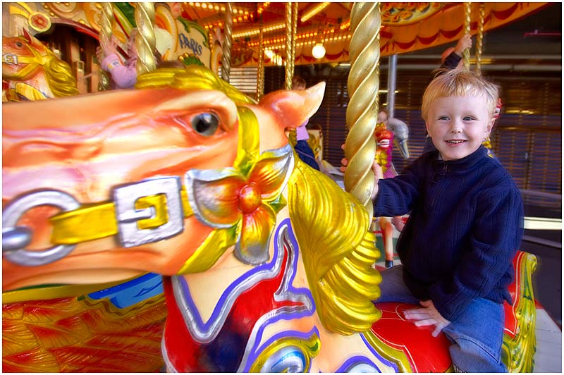 Luna Park, Saturday May 27th 2006. <br /> <br /> My three year old son, Tom, enjoys a ride on the carousel. This 100 year old fully restored steam driven carousel has hand carved wooden horses and an original 89 key Gavioli organ. <br />  <br /> EXIF DATA <br /> Canon 1D Mk II. EF 17-35 f/2.8L@17mm 1/40s f/4.5 ISO 200.