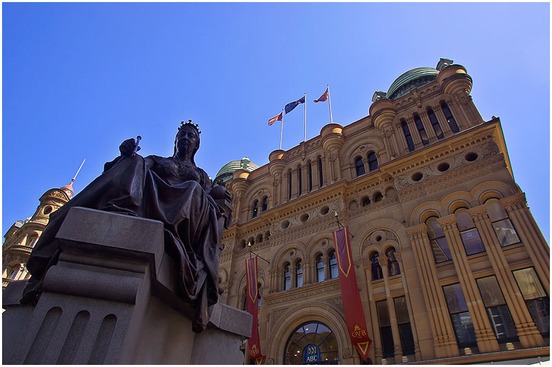 """Druitt Street, Friday November 10th 2006. </strong> The Queen Victoria Building, QVB, is a Victorian era (1896) shopping mall built in the Byzantine style and is celebrating its 20th anniversary since it was fully restored to its former glory. The statue of Queen Victoria has an interesting history. It is the work of Irish sculptor John Hughes. This statue stood outside the Irish Houses of Parliament in Dublin until 1947 and was given to the people of Sydney by the Irish Government in 1987. You can view a panorama of the street <a href=""""http://sydneywebcam.smugmug.com/photos/popup.mg?ImageID=109258379&Size=Original&popUp=1"""" target=""""_blank""""><strong><em>here</em></strong></a>.    EXIF DATA  Canon 1D Mk II. EF 17-35mm f/2.8L 1/60s f/5.6 ISO 200."""