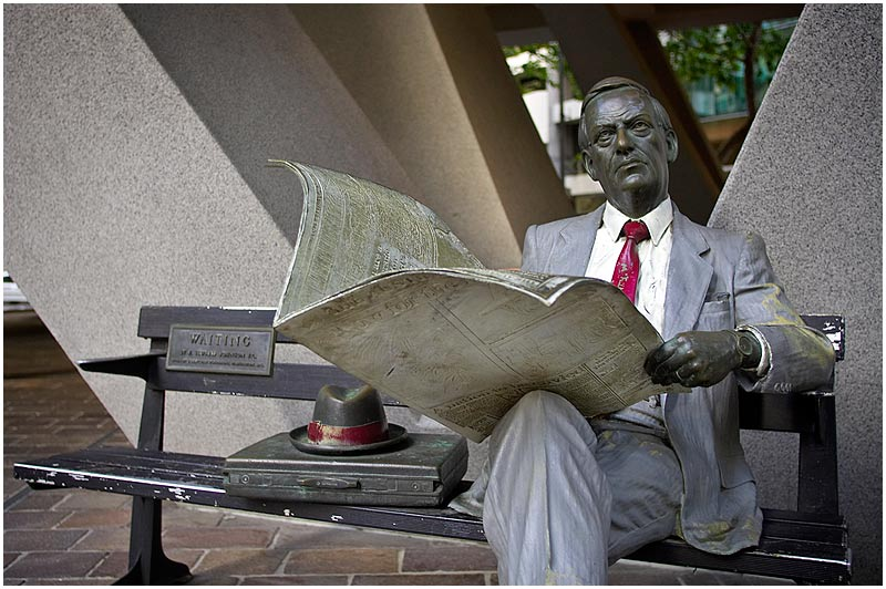 "Australia Square, Sunday November 5th 2006.  Waiting, a sculpture by J. Seward Johnson, depicts a businessman reading a newspaper. Johnson is most well known for his life-size cast bronze statues of people of all ages engaged in day-to-day activities. You can visit his website <a href=""http://www.sewardjohnson.com/site/index.html"" target=""_blank""><strong><em>here</em></strong></a>.    EXIF DATA  Canon 1D Mk II. EF 17-35 f/2.8L@28mm 1/50s f/2.8 ISO 200."