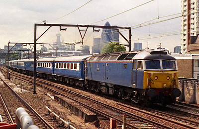 With a couple of familiar London landmarks dominating the skyline, 47712 'Artemis' accelerates past the Docklands Light Railway station at Shadwell with 5Z48 1538 Fenchurch Street-East Ham (28/06/2006)