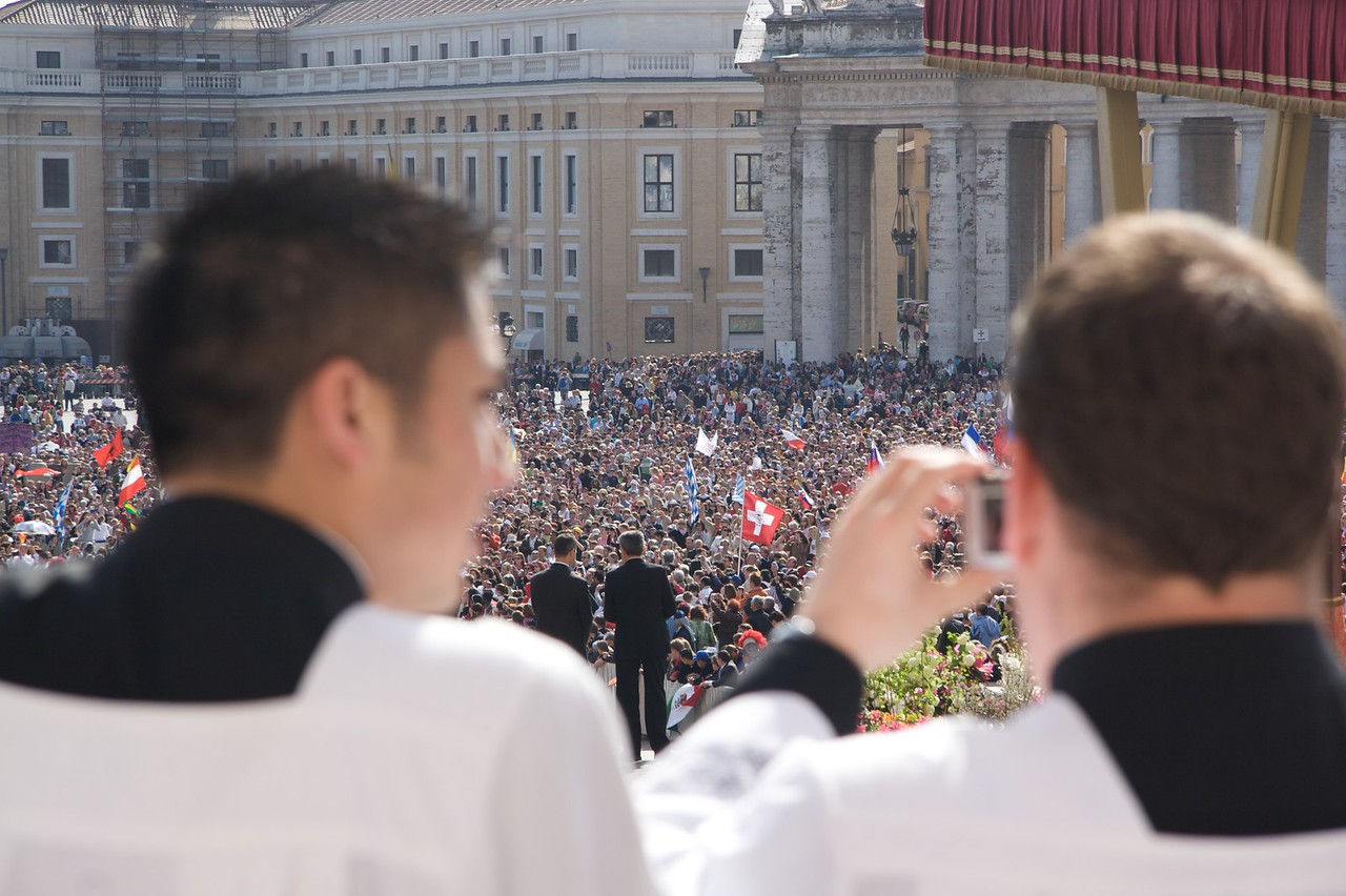 Two seminarians looking out at the crowds amassing in St Peter's Square for the Pope's Mass.