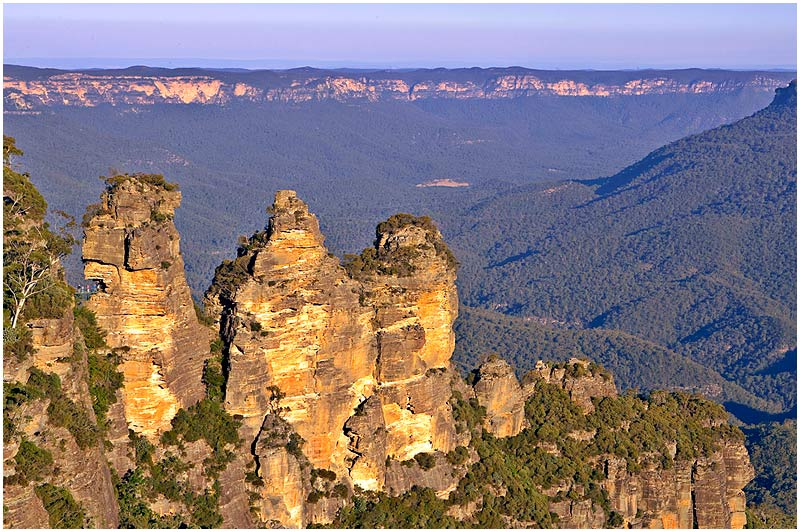 Katoomba, Sunday September 3rd 2006. <br /> <br /> The Three Sisters are a set of three closely-spaced sandstone pillars on the edge of the Blue Mountains plateau 110 km west of Sydney. They overlook the Jamison Valley, whose floor is over 300 m below them. Their name is derived from an Aboriginal legend which speaks of three sisters, Meeni, Wimlah and Gunedoo who were turned to stone. You can just make out some people on a walkway at the left pillar. <br />  <br /> <br /> EXIF DATA <br /> Canon 1D Mk II. EF 24-70f/2.8L@55mm 1/80s f/11 ISO 200.