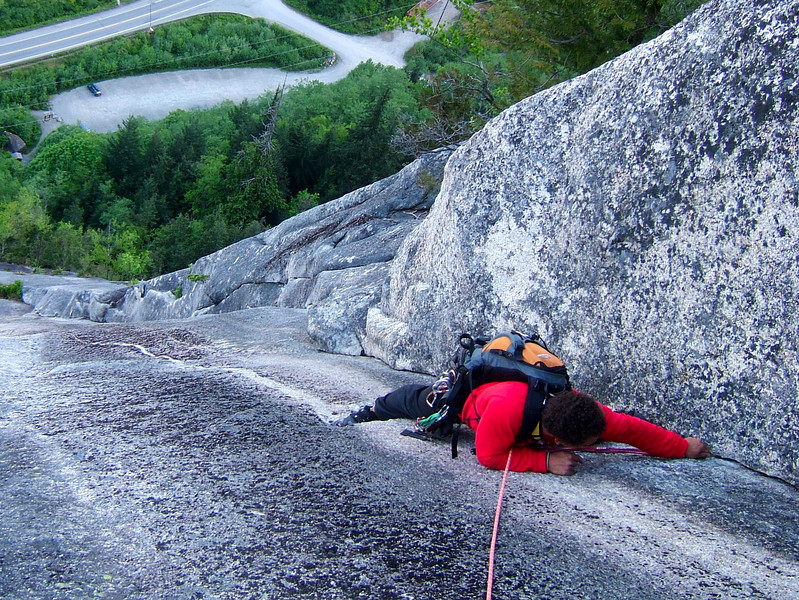 Kelsey reaches to recover a nut.  We got an early start on one of the most popular routes around, <i>Diedre 5.7</i>, as attested by the empty parking lot below.
