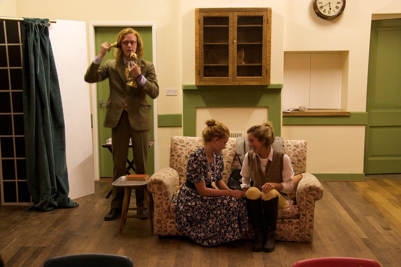 In rehearsal • Rory Lord Carmoyle (Will Dollard) answers a phone call from the police while Lady Carmoyle (Alice Robinson) and Jill Wyvern (Elise Carter) chat among themselves. In the first full dress rehearsal at the Kilburn Institute.