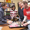 Craig Bowman (left), a professor at Rochester College, looks over photos of artifacts from an archeological dig in Israel that he and students (L-R) Nora Nasser, Jared Malone, and Adam Southerland were also at. The Oakland Press/DOUG BAUMAN