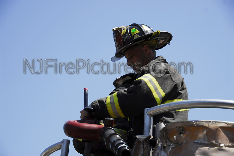Firefighter Bleichner prepares for tower ladder operations at a train car fire.