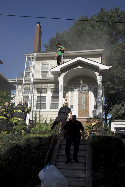 Passaic firefighters raise a ladder to rescue an occupant of the home.