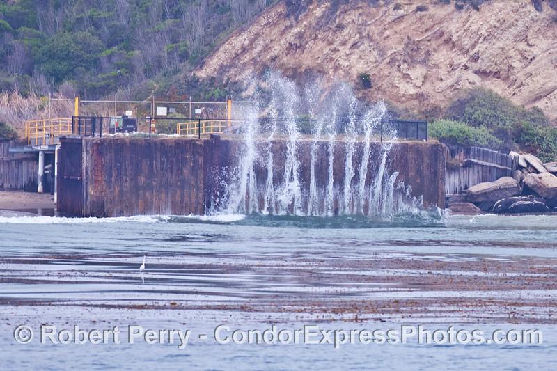 A small wave creates a big splash as it slams against a bulkhead guarding oil wells