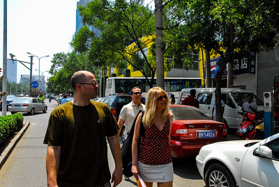 A photo of Patrick, Tim, and Corinne walking through a street in Beijing.