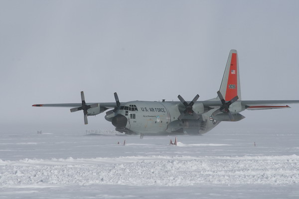 Hercules riding off the storm. Note the snow wall built to avoid the skis on the airplane snowing in. Also seen are the top of the old skiway markers that were left 2 m above snow surface in 2004.