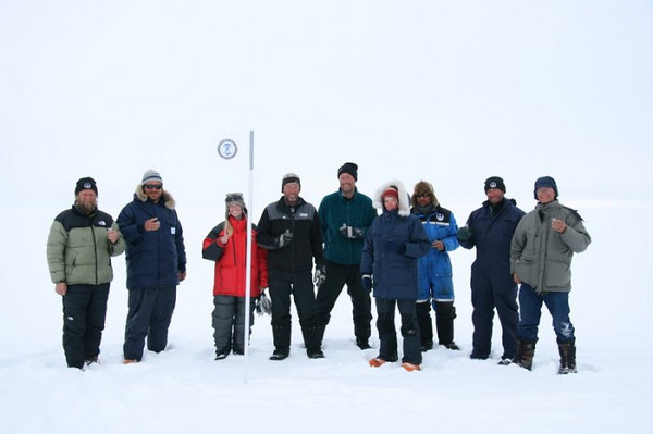 The whole gang at the NEEM ceremony<br /> Celebrating after deciding the exact drill location. The flag bears the logo of IPY. Left to right: J.P, Peter, Susanne, Sverrir, Lars, Maria, Steff, Simon, Claude