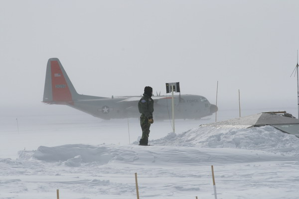 The C-130 stuck at NGRIP, a crew member on top of the buried Dome.
