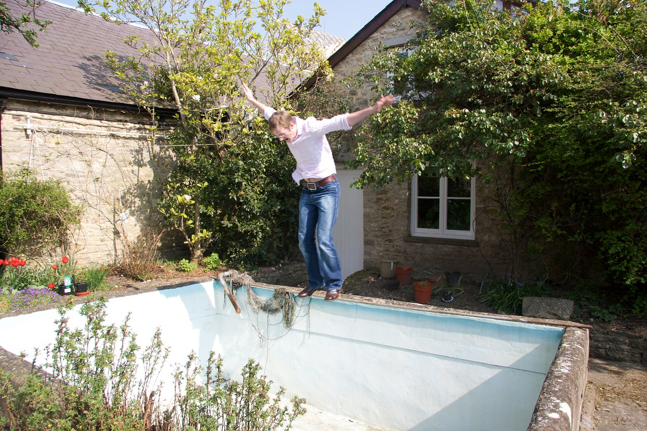 In mid-air • Greg leaps into the (empty) swimming pool.