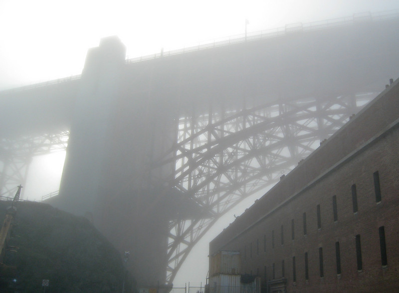 The Golden Gate Bridge looming over Fort Point in the fog.