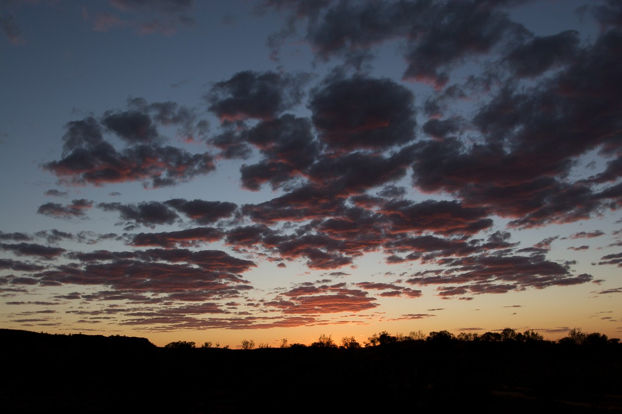 Sunset • The sun sets over Rainbow Valley in the Northern Territory, tinting the underside of the clouds pink.