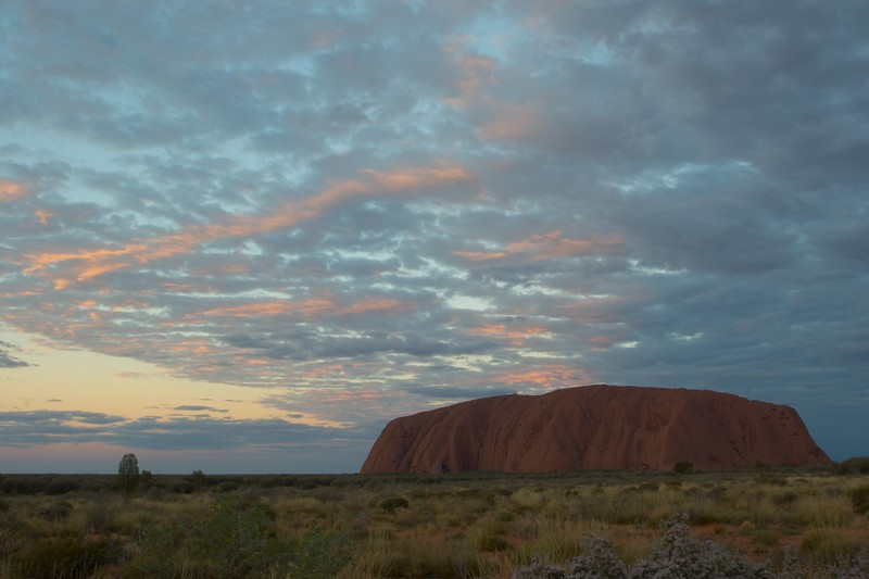 The changing face of Ayers' Rock 16 • It is frequently said that Ayers' Rock changes colour as the sun sets. This series of photos demonstrates how true that assertion is.<br /> <br /> Even after the sun has disappeared behind the horizon, it continues to leave colour in the clouds overhead.