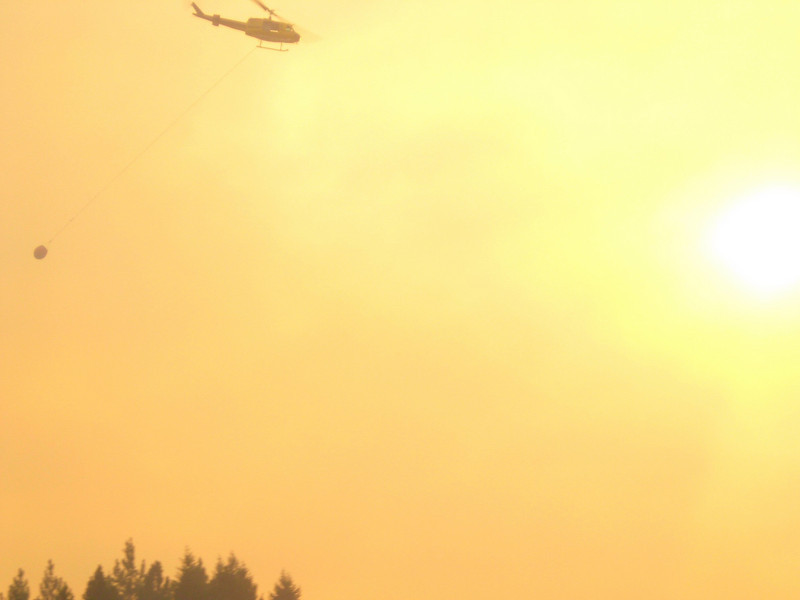 A helicopter bucket drop moves into position one afternoon as the fire makes a run toward the main camp.