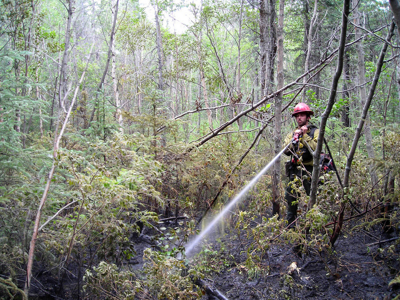 Showing the wear after some 16 hours of fire attack, Richard Harrop waters down the weeds.