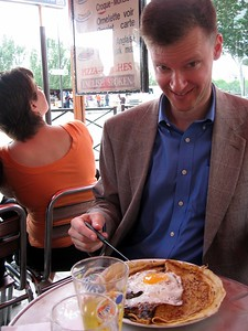 William enjoying a savory crêpe at a cafe along the Siene River in Paris