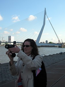 Kara snaps a photo of a fire truck, failing to notice the enormous bridge behind her