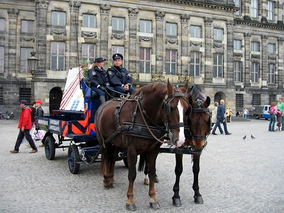 Mounted police officers in Amsterdam, carrying a sign warning of pickpocketers